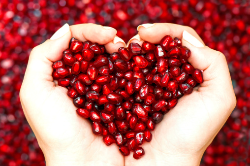 178590070-pomegranate-seeds-shaping-heart-in-hands