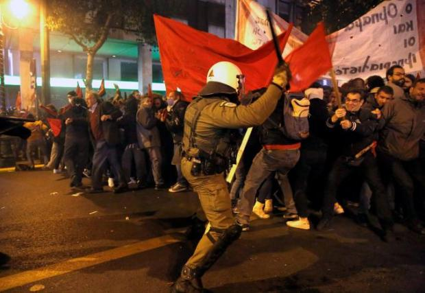 A riot policeman attacks protesters during a demonstration against the visit of U.S President Barack Obama, in Athens